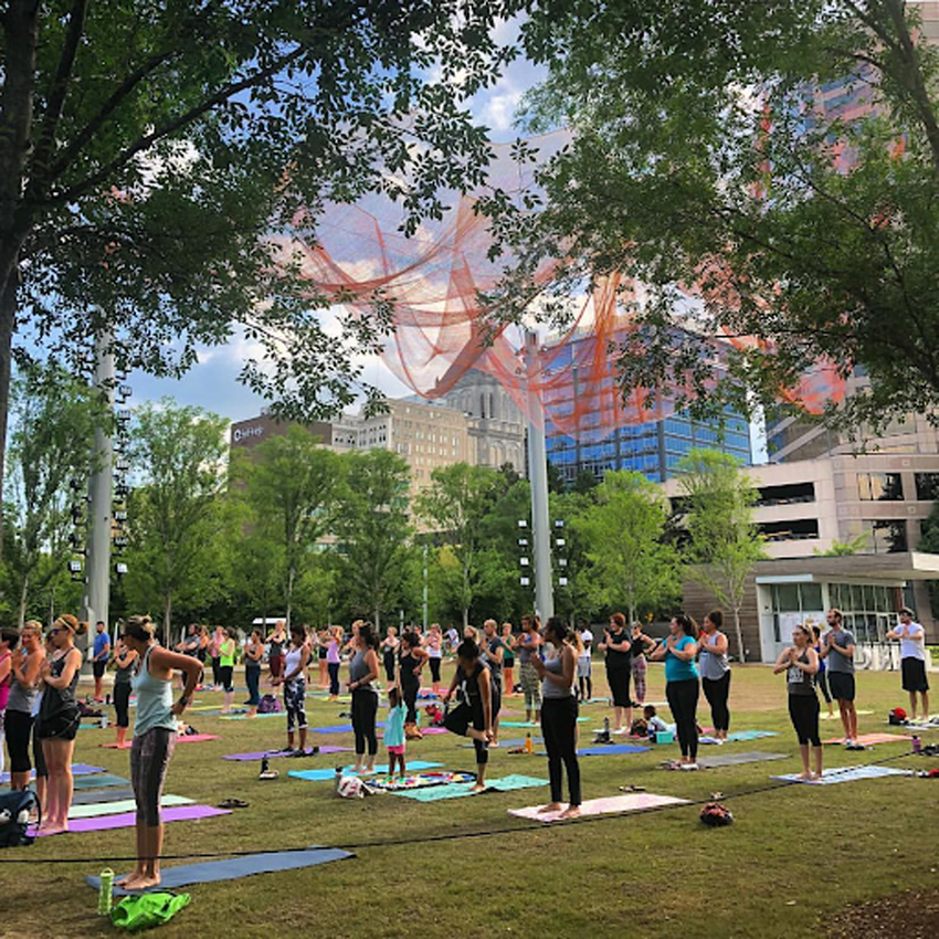 people in a park doing yoga